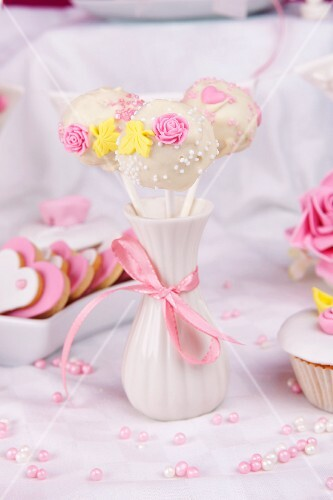 Three cake pops decorated with sugar roses in a vase