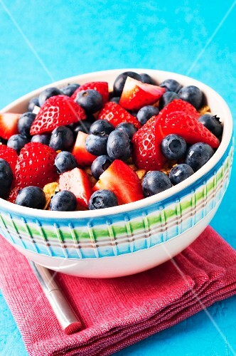 A bowl of strawberries, blueberries and muesli
