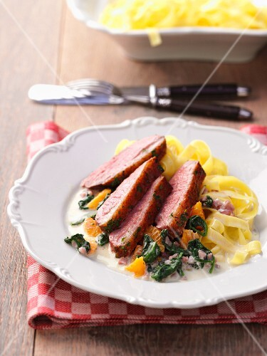Duck breast with oranges, spinach and tagliatelle