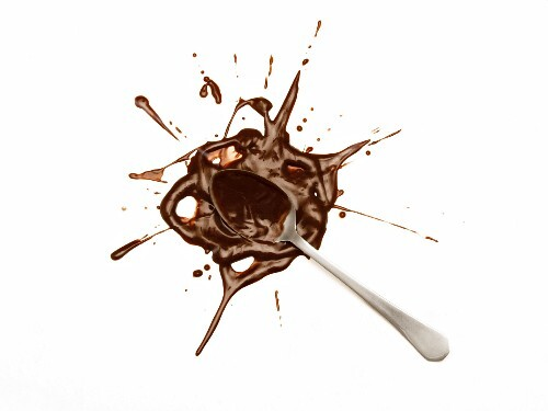 A spoon in a splat of chocolate