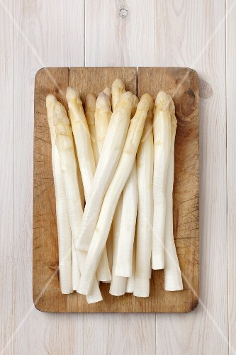 Peeled white asparagus on a chopping board