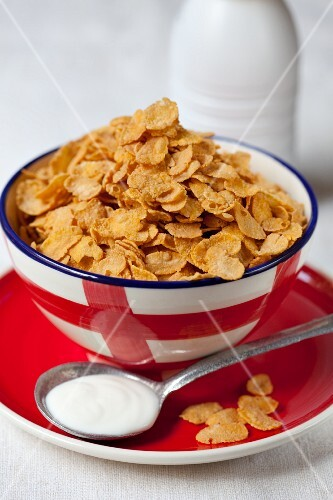 A bowl of cornflakes with a spoonful of yogurt