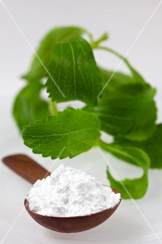 Stevia leaves and white stevia powder on a wooden spoon