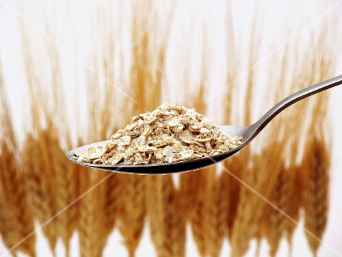 A spoonful of oats with ears of wheat in the background