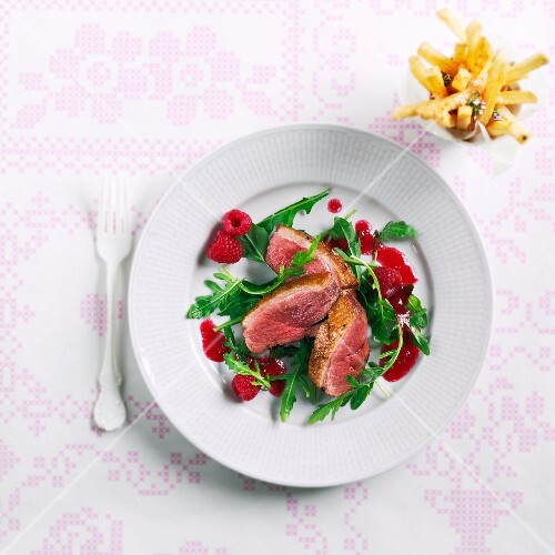 Duck breast with rocket and a raspberry vinaigrette and chips