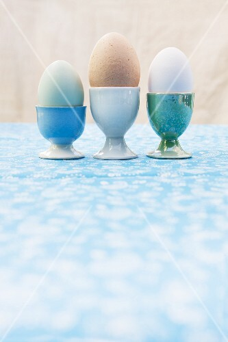 Three eggs (green, brown, white) in egg cups