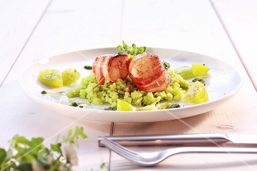 Scallops wrapped in bacon on green rice