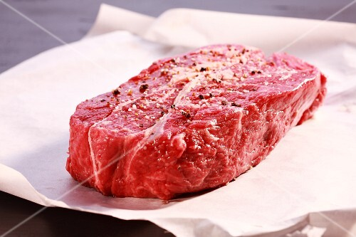 A raw, seasoned beef steak
