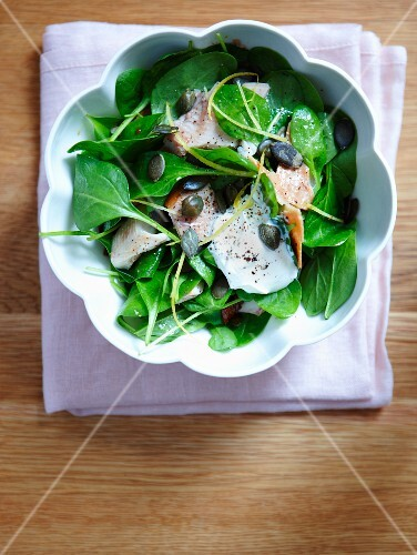 Spinach salad with salmon, pumpkin seeds and lemon cream