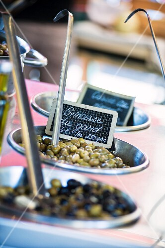 Various types of preserved olives at a market