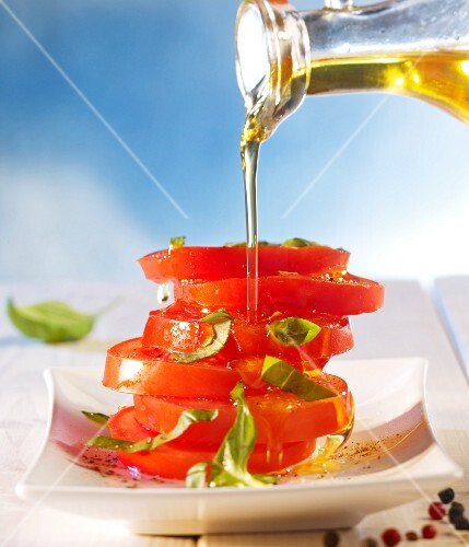 Olive oil being poured over a stack of seasoned tomato slices