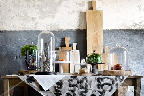 Table with chopping boards leaning on wall and groceries and kitchen utensils under glass covers