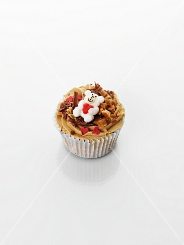 A cupcake decorated with caramel, a teddy bear and hearts