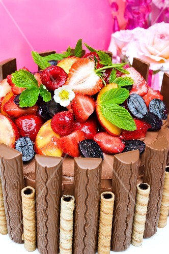 Chocolate cake with chocolate bars, wafers, summer fruits and strawberry fruits