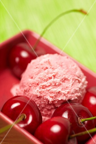 A scoop of cherry ice cream with fresh cherries