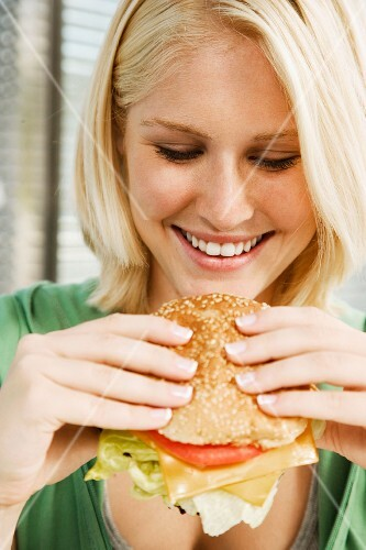 Teenage girl eating a hamburger in a diner
