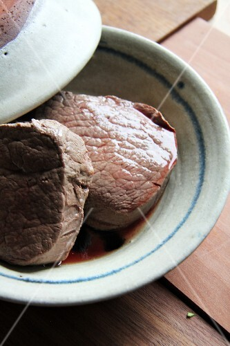 Two pieces of beef fillet in a bowl with a lid