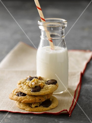 Three Stacked Chocolate Chip Cookies with a Bottle of Milk with a Straw