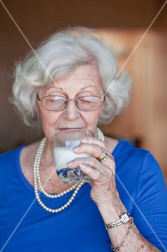 An older woman drinking a glass of milk