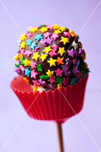 A cake pop decorated with coloured stars
