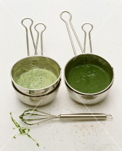 Green herb sauce in saucepans