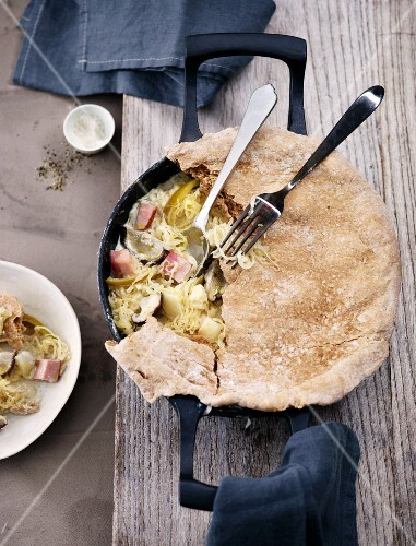 Winter vegetables with smoked pork covered in bread dough