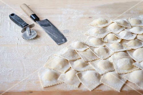 Fresh, homemade ravioli on a floured work surface
