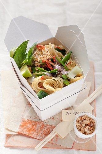 A box of noodles with bok choy and peanuts
