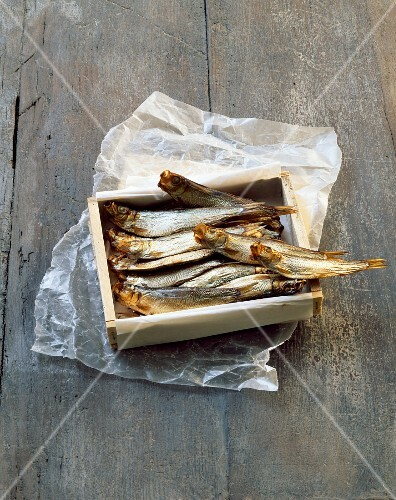 Smoked sardines in a wooden crate