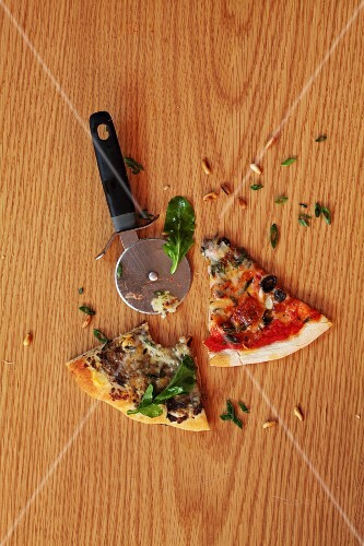 Slices of pizza and a pizza wheel on a wooden surface