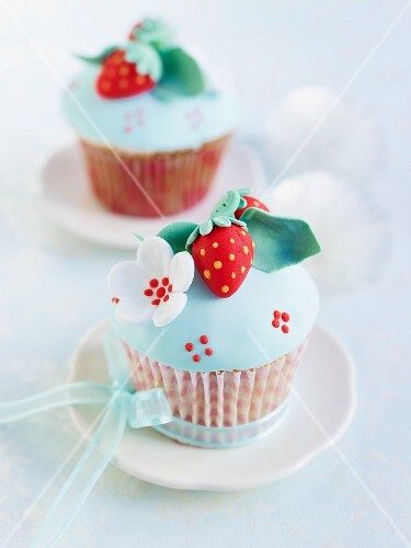 Cup cakes decorated with blue icing and marzipan decorations