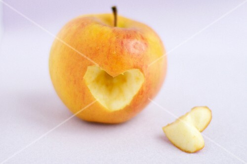 An apple with a heart-shape cut out of it