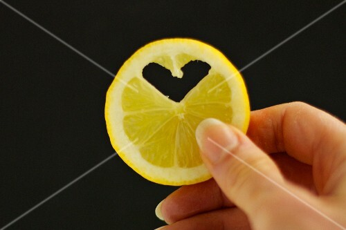 A slice of lemon with a heart-shaped piece cut out of it