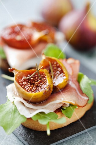 Crostini topped with rocket, raw ham, oven-baked balsamic figs and rosemary