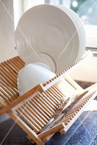 weisses geschirr und silbermesser auf abtropfgestell aus hellem holz bild kaufen 11145704. Black Bedroom Furniture Sets. Home Design Ideas