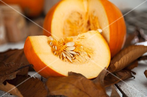 A sliced pumpkin on autumnal leaves