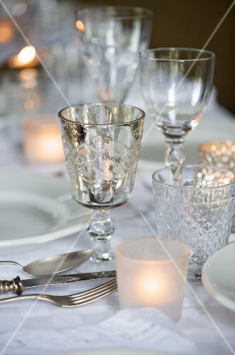 Festively set table with various glasses and tealight holders