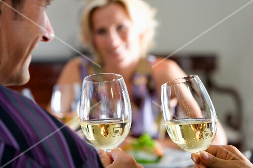 Couple holding glasses of white wine at table, woman smiling in background