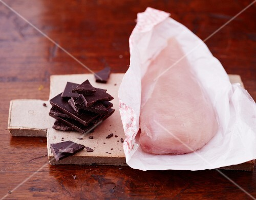 Raw chicken breast on a piece of paper and dark chocolate on a wooden board