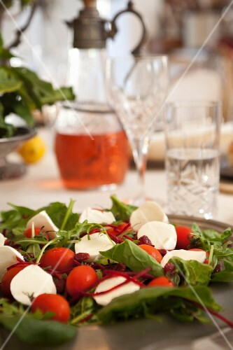 Tomatoes with mozzarella and rocket on a table laid for a meal