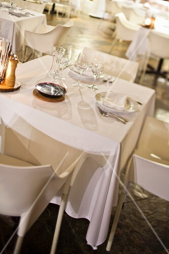 Set tables with white tablecloths and white designer chairs in dining room