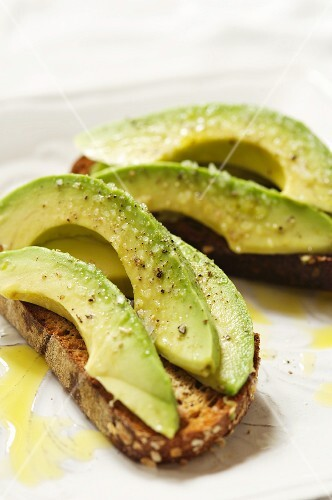 Sliced Avocado on Whole Grain Bread Topped with Salt, Pepper, Olive Oil and Lemon Juice