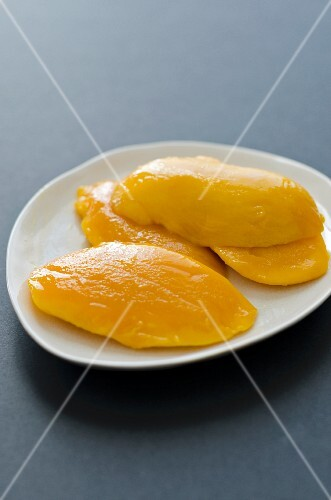 Several slices of mango on a plate