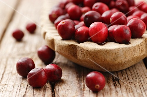 Cranberries in a wooden dish on a wooden surface