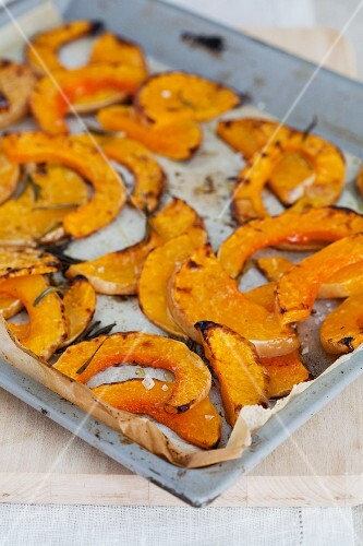 Slices of roasted pumpkin on a baking tray