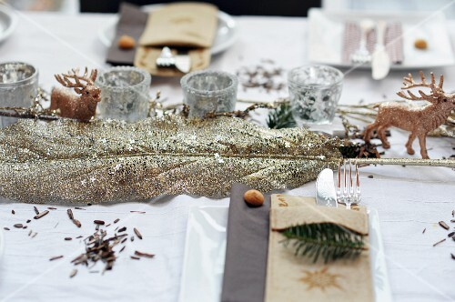 Christmas table decorations: leaf covered in gold glitter, stag ornament and silver tealight holders