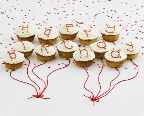Cupcakes with white glaze and letters spelling out Happy Birthday
