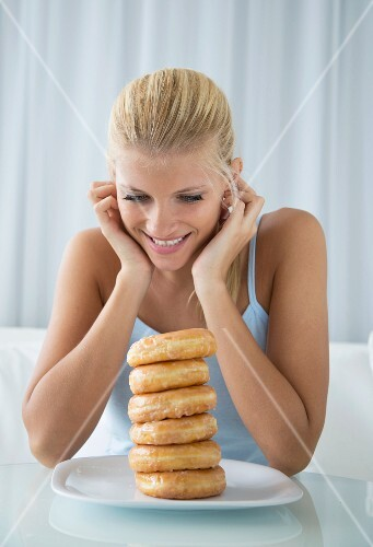 A blonde woman looking at a stack of doughnuts