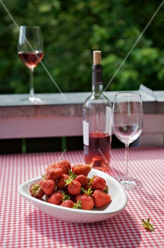 A bowl of strawberries and some rosé wine on a table on the balcony, the table covered with a gingham tablecloth