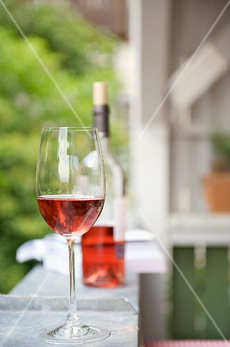 a glass of red wine on the balcony railing